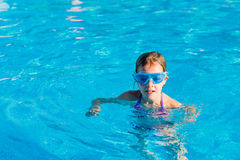 happy girl in blue goggles swimming in the swimming pool Stock Photography