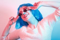 Girl in blue wig. Happy girl in blue wig and sunglasses on multicolor background smiling Stock Images