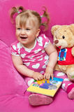 Happy girl with book. Happy young girl with book and teddy bear; pink background Royalty Free Stock Photos