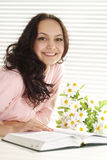 Happy girl with a book sitting at a table  Stock Images