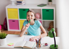 Happy girl with book writing to notebook at home Stock Photography