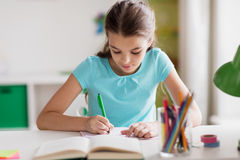 Happy girl with book writing to notebook at home Stock Image