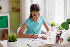 Happy girl with book writing to notebook at home Royalty Free Stock Photos