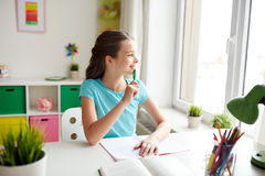 Happy girl with book writing to notebook at home Royalty Free Stock Images
