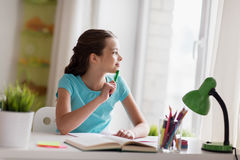 Happy girl with book writing to notebook at home Stock Images