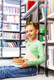 Happy girl with books sits on floor in library Stock Photography