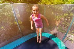 Happy girl bouncing up on the trampoline outdoors royalty free stock photography
