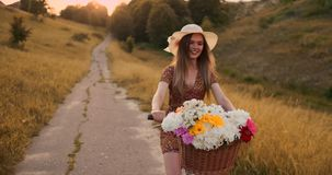 Happy girl with a bouquet of flowers riding a bike in a hat and a summer short dress. A girl in a dress riding a bike with flowers in a basket and laughing stock footage