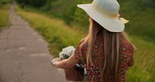 Happy girl with a bouquet of flowers riding a bike in a hat and a summer short dress. A girl in a dress riding a bike with flowers in a basket and laughing stock video
