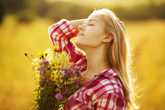 Happy girl with a bouquet of wild flowers Stock Photography