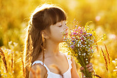 Happy girl with a bouquet of wild flowers Stock Photo