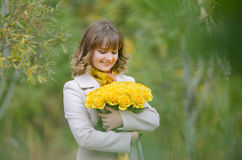 Happy girl with a bouquet of yellow roses Royalty Free Stock Photography
