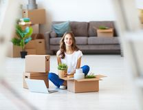 Happy girl with boxes moves to new apartment stock photos