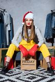 happy girl in boxing gloves and santa hat sitting with shopping bags and clothes around, black stock photography