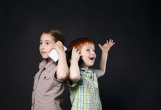 Happy girl and boy, children speak on mobile phones. Portrait of happy, smiling girl and boy speak on mobile phones at black background. Positive and emotional Royalty Free Stock Photo