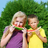 Happy girl and boy eating watermelon Stock Photos