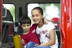 Happy Girl and Boy in Firefighter Car. Enjoying Outdoors royalty free stock images