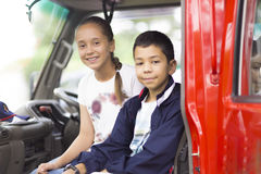 Happy Girl and Boy in Firefighter Car. Enjoying Outdoors stock photography