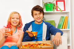 Happy girl and boy hold pizza pieces on white sofa Stock Image