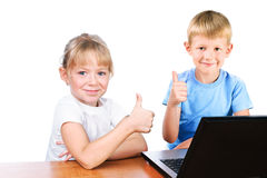 Happy girl and boy at laptop with thump up sign Stock Images