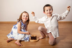 Happy girl and boy playing a board game Stock Photos