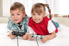 Happy girl and boy playing a video game stock photos