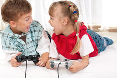 Happy girl and boy playing a video game Royalty Free Stock Photography