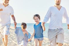 Beach Summer Vacation Generations. Happy girl and a boy running on the beach along their father and grandfather Stock Image