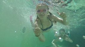 Girl and boy swimming under water. Happy girl and boy swimming under water stock footage
