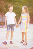 Happy girl and boy taking walk together in park Royalty Free Stock Photos