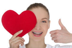 Happy girl with braces and heart. Isolated on white Royalty Free Stock Photo
