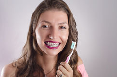 Happy girl with braces holding toothbrush Royalty Free Stock Image