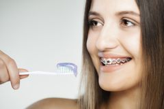 Happy girl with braces and toothbrush. Attractive caucasian girl with braces, holding toothbrush Royalty Free Stock Images