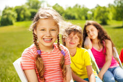Happy girl with braids and her friends sitting Stock Image