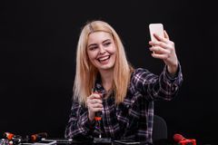 Happy girl breaks smartphones with a tool and makes selfie on a mobile phone. On a black background. stock photography