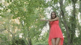 Happy girl in a bright pink dress standing on the stock video footage