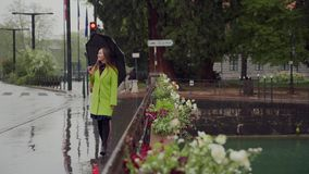 Happy girl in bright yellow coat with an umbrella walks across the bridge through a canal in Annecy in rainy weather. France. Portrait 4k stock footage