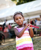 Happy Girl With Broom. A young girl smiling and playing with a colorful broom at a broomstick festival in Arcola, Illinois Royalty Free Stock Photo