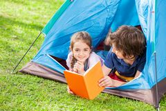 Happy Girl With Brother Reading Book In Tent Stock Photo
