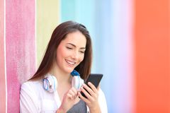 Happy girl browsing phone content in a colorful place stock photography