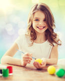 Happy girl with brush coloring easter eggs. Easter, holiday and child concept - happy girl with brush coloring easter eggs over lights background royalty free stock photos