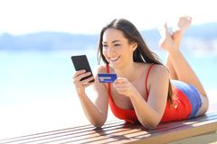 Happy girl buying online with phone and credit card stock photos