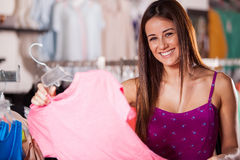 Happy girl buying some clothes. Cute young woman looking at some blouses in a clothing store stock photography