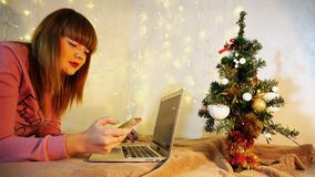 Cheerful female person talking on phone and typing message on la. Happy girl calling boyfriend to congratulate on Christmas. Gladden woman writing message to Stock Photos