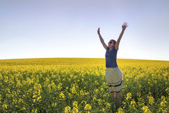 Happy Girl among Canola Plants under Blue Sky Royalty Free Stock Image