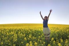 Happy Girl among Canola Plants under Blue Sky Royalty Free Stock Image