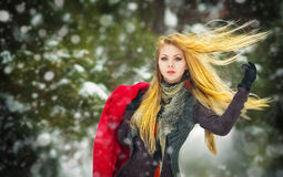 Happy girl with cap and gloves playing with snow in the winter landscape Royalty Free Stock Photos