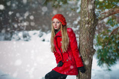 Happy girl with cap and gloves playing with snow in the winter landscape Stock Photo