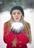 Happy girl with cap and gloves playing with snow in the winter landscape Stock Photography