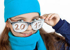Happy girl in a cap and scarf in funny glasses with the inscription 2017 Royalty Free Stock Photo